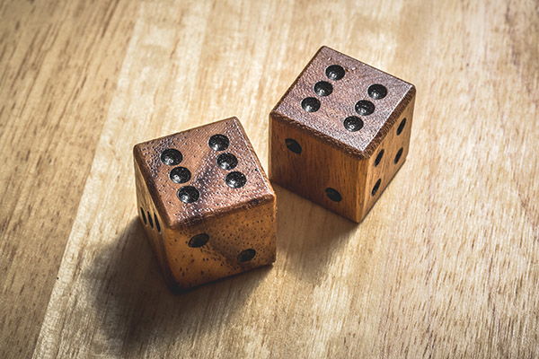 Two wooden dice with the number 6 on a table.