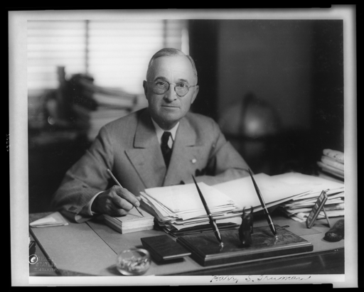 Harry Truman at his desk, courtesy Wikimedia Commons by Chase-Statler, Washington.